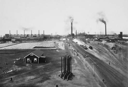 Blast Furnaces in the middle; refinery on the right; zinc plant on the left. Note ore trains on right and stack of refined lead on left.