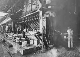 Tapping base bullion, impure lead and slag. Slag is flowing into the pot on the right and lead into moulds on the left. The inclined pipes convey the air blast to the furnace.